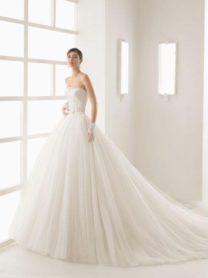 Открытое свадебное платье притягивает взгляды эффектным корсетом. Он полностью покрыт фактурной кружевной тканью, прямой лиф прекрасно подчеркивает область декольте, а на спинке вырез становится более глубоким.  Не менее красива и многослойная юбка А-силуэта из воздушной ткани. Сзади ее украшает шлейф, а по всей длине – множество вертикальных складок.