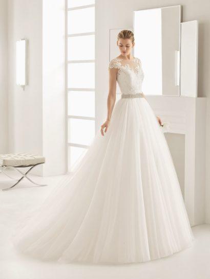 Сдержанное и утонченное свадебное платье создает роскошный силуэт благодаря объемной юбке А-кроя. Акцентировать ее воздушность помогает не только шлейф, но и широкий серебристый пояс на талии.  Верх с традиционным лифом в форме сердечка покрыт полупрозрачной тканью с аппликациями. Они создают широкие фигурные бретели на плечах и украшают спинку платья.