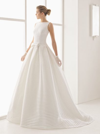Уникальное свадебное платье создано из плотной ткани с рисунком из горизонтальных полос.  Такая текстура придает классическому силуэту «принцесса» яркую индивидуальность.  Образ не перегружен лишними деталями – платье украшает лишь небольшой бантик на линии талии.  Закрытый верх с вырезом «бато» и элегантными бретелями уравновешивает глубокое V-образное декольте на спинке.