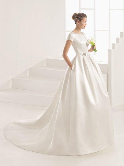Утонченное сияние плотного атласа покорит даже самую взыскательную невесту.  Дополненный длинным шлейфом пышный крой придает свадебному платью необходимую торжественность.  Оригинальный верх оформлен коротким рукавом прямого кроя.  Округлый вырез декорирован по краю вышивкой.  Сзади вышивка становится более плотной и выразительной, украшая драматичное V-образное декольте.