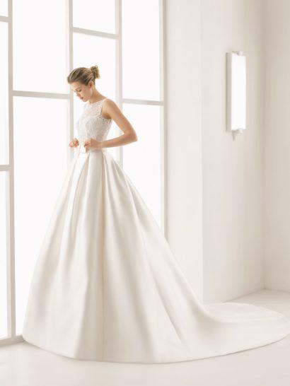 Очаровательное свадебное платье пышного кроя красиво объединяет в одном образе сияющую гладкость атласа и романтичное переплетение кружева.  Выразительный силуэт с длинным шлейфом сразу же создает особенную атмосферу.  Талию выделяет широкий атласный пояс с крупным бантом спереди.  Лиф с элегантным вырезом покрыт слоем фактурного кружева, которое декорирует и спинку свадебного платья.