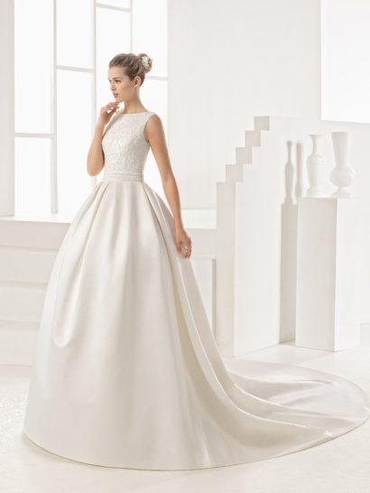 Оригинальное свадебное платье пышного кроя привлекает внимание сразу двумя деталями: оформлением спинки и сложным кроем юбки.  Сзади платье открыто до талии, вырез оформлен тонкой тканью с крупными кружевными аппликациями.  Это красиво смотрится в сочетании с закрытым лифом.  Юбка пышного кроя украшена шлейфом, спускающимся от талии выразительными вертикальными волнами атласной ткани.