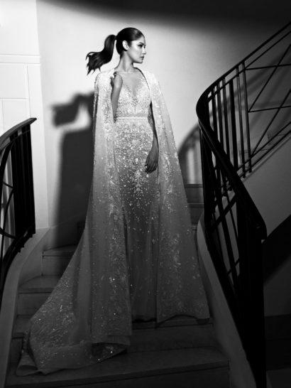 Великолепное свадебное платье потрясает совершенством каждой детали.  Изысканная вышивка нитью и бисером покрывает ткань почти по всей длине прямого силуэта, придавая ей чарующую фактуру.  Дополнить декольте с иллюзией полу-прозрачности помогает потрясающая длинная накидка из тонкой ткани, украшенная такой же вышивкой, что и платье.  Она спускается шлейфом и позволяет быстро преображать образ.  Свадебные платья Zuhair Muradэксклюзивно представлены в салоне Виктория    В НАЛИЧИИ