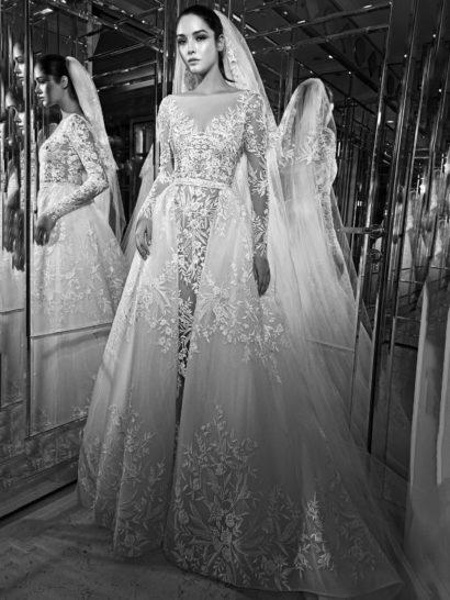 Чувственное свадебное платье с пышной верхней юбкой объединяет два образа в одном. Съемная юбка украшена по нижней части подола крупным цветочным узором вышивки, дополненным стразами.  Не менее выразительная вышивка украшает и прямое платье, создавая элегантную иллюзию полупрозрачности. Фигурный V-образный вырез декольте с длинным облегающим рукавом смотрятся стильно и женственно.  Свадебные платья Zuhair Muradэксклюзивно представлены в салоне Виктория