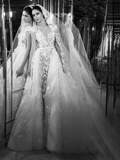 Великолепное свадебное платье с иллюзией полупрозрачности обрисовывает силуэт облегающим верхом и задает атмосферу торжественности воздушной юбкой сложного кроя. Короткий рукав красиво сочетается с соблазнительным фигурным декольте.  По всей длине свадебное платье украшено кружевными аппликациями с бисерной вышивкой. Нежный узор хорошо выделяется на тонкой ткани верха и придает объем пышному подолу.  Свадебные платья Zuhair Muradэксклюзивно представлены в салоне Виктория