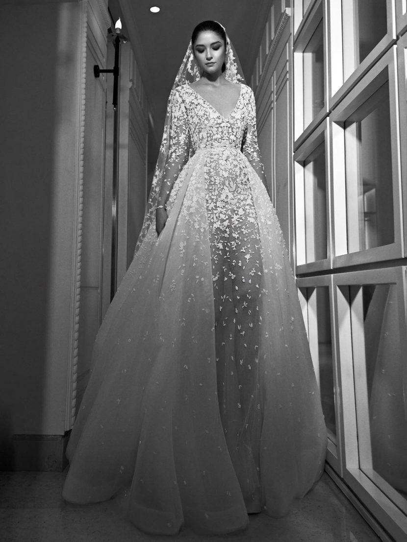 Эффектное свадебное платье с глубоким декольте и многослойной пышной юбкой.
