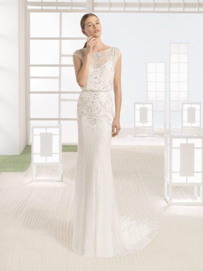 Безупречно утонченное свадебное платье очерчивает силуэт прямым кроем.  Закрытый верх с коротким рукавом и округлым вырезом оформлен нежным рисунком вышивки.  Такой же фактурный декор покрывает и верхнюю часть подола, спускаясь от талии.  Спинку свадебного платья оформляет полупрозрачная ткань, дополненная узким разрезом, спускающимся почти по всей длине.  Небольшой шлейф из тонкой ткани привносит в образ еще больше романтичности.