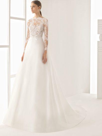 Сдержанное свадебное платье, сочетающее в себе лаконичность и романтичное настроение. Закрытый верх с длинным рукавом и воротником-стойкой трогательно оформлен кружевом с мелким рисунком.  От талии, выделенной узким поясом с бантом, спускается юбка А-силуэта. Ее украшением служит лишь стильный полукруг шлейфа, что уравновешивает выразительность декора верха.