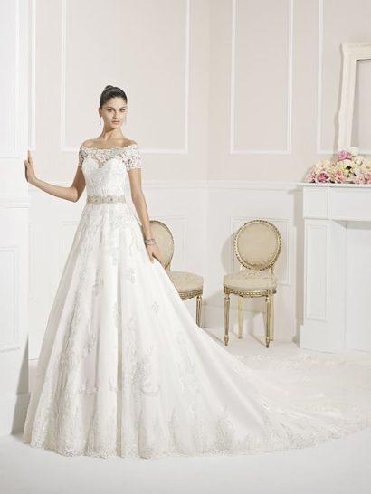 Стильное свадебное платье притягивает взгляды богатством фактуры. Плотная ткань юбки А-силуэта прекрасно оттеняет кружевные аппликации, настраивающие на романтичный лад.  Отдельного внимания заслуживает изысканное оформление декольте. Над плотным лифом в форме сердца – слой кружева, создающий портретное декольте и короткие полупрозрачные рукава.