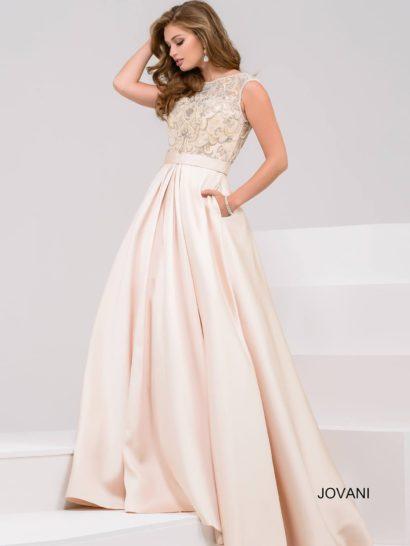 Нежное вечернее платье розового цвета подойдет для самых особенных моментов в жизни. Пышная юбка сразу же создает нужное настроение. Дополнить ее помогают скрытые карманы и широкий пояс.  Закрытый верх оформлен полупрозрачной кружевной тканью, создающей округлый вырез. На спинке ткань использована без подкладки, что смотрится невероятно притягательно.