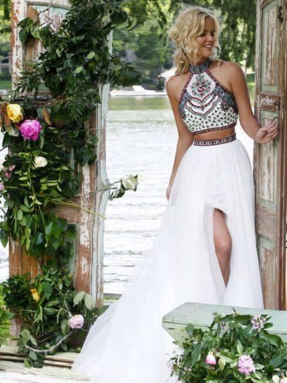 Незабываемый образ создаст вечернее платье с коротким топом и оригинальной юбкой. Топ с американской проймой очерчивает шею, он полностью декорирован разноцветным бисерным узором.  Юбка дополнена расшитым бисером поясом. Она открывает ноги высокими разрезами, поднимающимися до самой середины бедра.