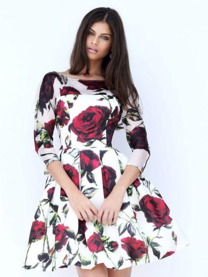 Закрытое вечернее платье создано для самой смелой девушки, не боящейся подчеркивать свою чувственность. Изюминкой оригинального образа является крупный цветочный принт с алыми розовыми бутонами.  На спинке – эффектное V-образное декольте, уравновешенное длинным рукавом и вырезом «бато» спереди. Юбка до середины бедра декорирована крупными вертикальными складками.