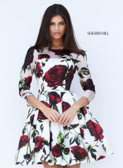 Короткое вечернее платье с эффектным цветочным принтом и длинным рукавом.