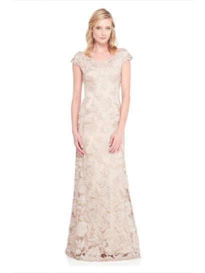 Невероятно женственное вечернее платье бежевого цвета с коротким фигурным рукавом и сдержанным вырезом с ажурным краем. По всей длине платье покрыто крупным цветочным узором кружевной отделки.  В роли подкладки – бежевая трикотажная ткань, обеспечивающая комфорт и элегантность. Длинная юбка А-силуэта великолепно завершает силуэт и наполняет платье праздничным настроением.