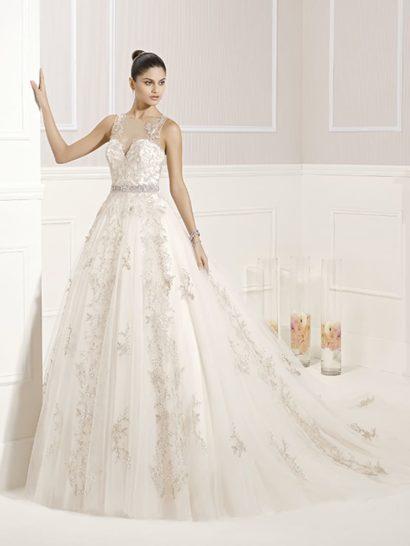 Изысканное свадебное платье каждой деталью настраивает на нужный лад. Женственное глубокое декольте укрыто полупрозрачной тканью, тонкая вставка закрывает и округлый вырез на спине, выступая основой для бисерной вышивки.  Потрясающая многослойная юбка А-силуэта спускается вертикальными волнами и переходит сзади в эффектный полупрозрачный шлейф.