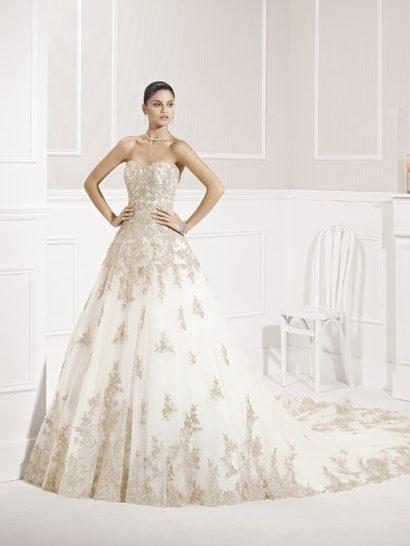 Царственное свадебное платье с силуэтом «принцесса» приковывает внимание длинным шлейфом. Его край покрыт плотным слоем золотистой вышивки, создающей ажурный цветочный мотив.  Такая же отделка покрывает платье и по подолу, и по корсету. Элегантный открытый лиф в форме сердечка обрисовывает декольте и подчеркивает хрупкую линию обнаженных плеч. Сзади спина открыта V-образным вырезом.