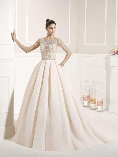 Деликатный розовый оттенок ткани служит особенным украшением впечатляющего свадебного образа. Роскошная юбка «принцесса» прекрасно дополняет облегающий верх свадебного платья.  Прозрачная ткань полностью покрывает корсет, создавая рукава длиной в три четверти. Она служит основой для сияющей серебристой вышивки, декорирующей как лиф, так и спинку платья.