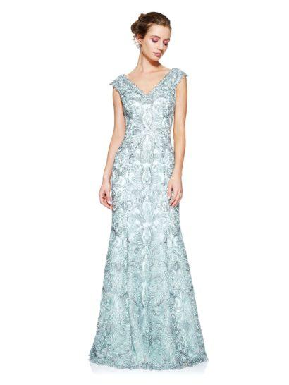 Впечатляющее серо-голубое вечернее платье околдовывает необычной фактурой плотной ткани. Область декольте изящно очерчивает небольшой V-образный вырез, обрамленный широкими бретелями, слегка спущенными с плеч.  На спинке располагается вырез такой же формы. Деликатный объем юбки А-силуэта, спускающейся до самого пола, позволяет подчеркнуть торжественность момента.