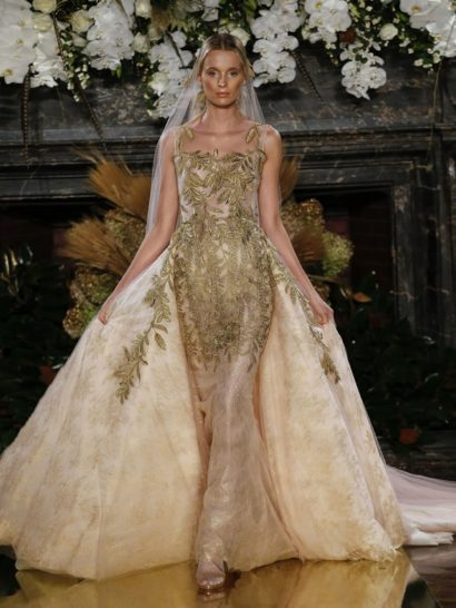Свадебное платье силуэта «русалка» выполнено из полупрозрачного тюля и кружева – поверх располагается вышивка в бледно-розовом и золотом тонах, которые идеально сочетаются друг с другом. Иллюзия прямого выреза и романтичная прозрачная отделка под кружевным цветочным узором великолепно украшают образ. Длинный торжественный шлейф оформлен таким же золотистым узором в растительном стиле.