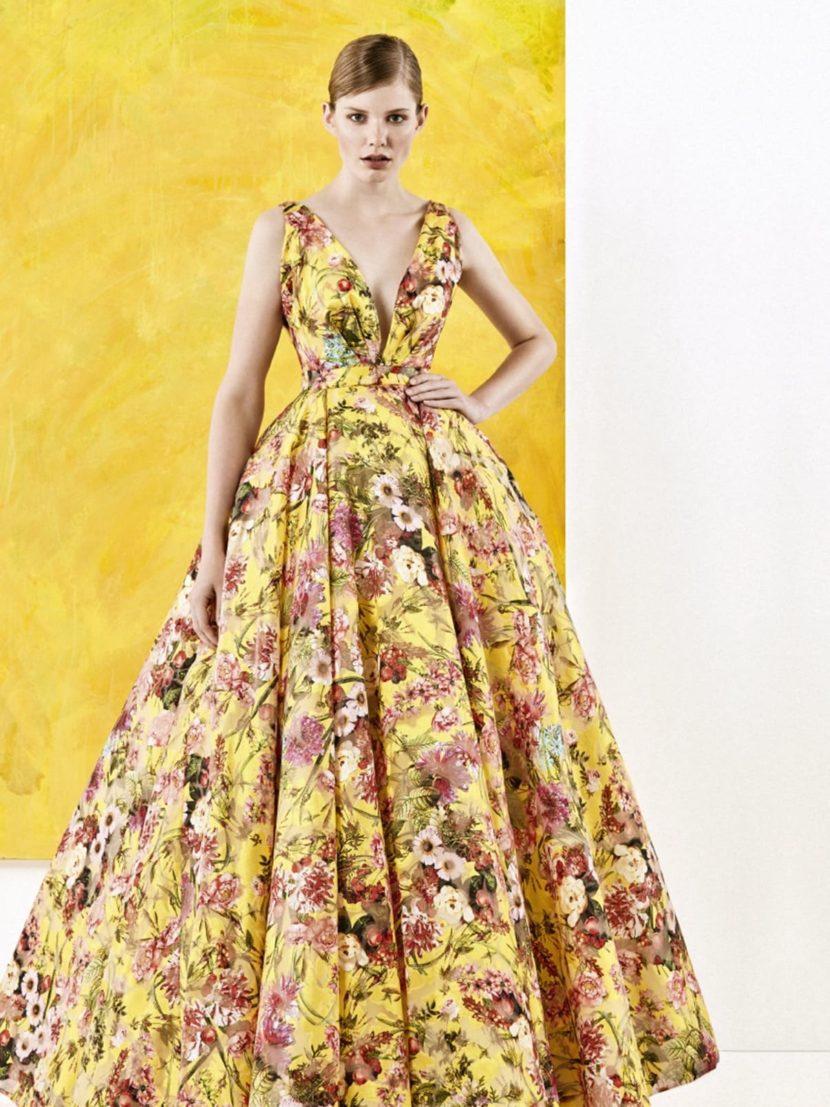 Желтое вечернее платье с выразительным цветочным принтом и глубоким декольте.