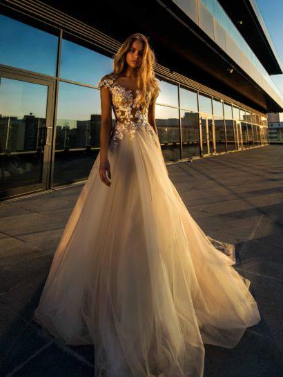 Романтичное свадебное платье пышного кроя в оттенке слоновой кости. Полупрозрачный верх с глубоким декольте драматично декорирован крупными аппликациями из плотной белой ткани. Такая же отделка обрамляет и вырез на спинке. Элегантный шлейф прекрасно завершает многослойную юбку из фатина.