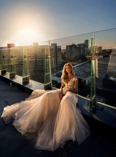 Свадебное платье с многослойным подолом и полупрозрачным лифом с аппликациями.