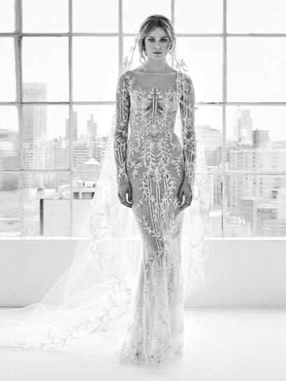 Впечатляющее дизайнерское свадебное платье-трансформер. Основой является прозрачное платье прямого кроя с длинным рукавом и округлым вырезом. Оно по всей длине декорировано деликатным цветочным мотивом аппликаций.  Преображает образ пышная верхняя юбка с кружевным декором. Она дополнена элегантным широким поясом.
