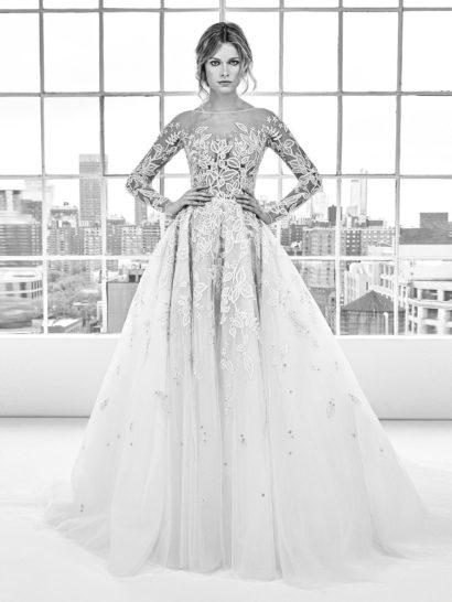 Сногсшибательное свадебное платье А-силуэта – для невест, предпочитающих драматичный стиль. Верх выполнен из прозрачной ткани, покрытой крупным цветочным узором. Такая же отделка покрывает и облегающие рукава, и верх многослойного подола.  Воздушная юбка из белого тюльмарина создает особенное настроение, спускаясь выразительными волнами и образуя шлейф сзади.
