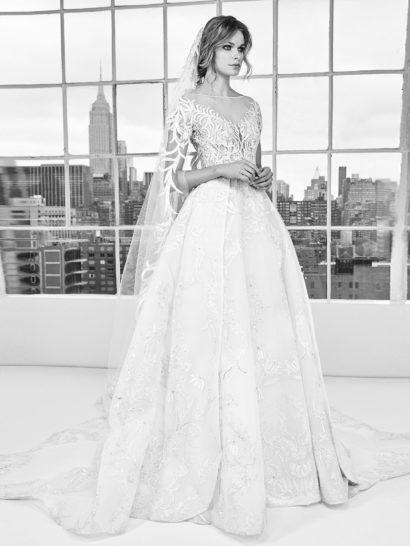 Роскошное свадебное платье, полное женственности и торжественного настроения. Эффектная юбка спускается плотными складками и переходит в шикарный полукруг шлейфа.  Облегающий фигуру верх смело оформлен прозрачной тканью, покрытой лишь кружевными аппликациями. Они создают элегантное V-образное декольте с фигурным краем.