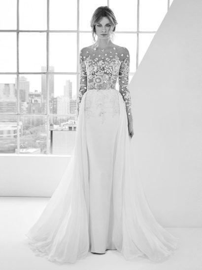 Изысканное свадебное платье мягко очерчивает силуэт прямой юбкой. Верх с длинным рукавом создан из прозрачной ткани, покрытой кружевом и вышивкой.  Лаконичный подол деликатно украшен сверху кружевным декором. Сзади его дополняет шлейф, идущий от самой линии талии и ниспадающий по бокам.