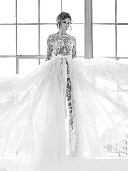 Эксцентричное свадебное платье-трансформер воплотит мечту самой взыскательной невесты.  Основой образа служит соблазнительный комбинезон из прозрачной ткани, полностью покрытой кружевом.  Длинный рукав и округлый вырез под горло гармонично сочетаются с чувственной тканью.  Наполнить торжественностью наряд помогает воздушная верхняя юбка.  Линию талии она выделяет широким поясом, украшенным объемным бантом.    В НАЛИЧИИ