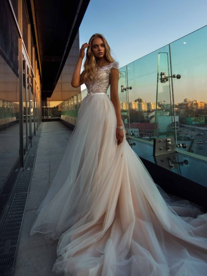 Великолепное свадебное платье с чарующим силуэтом. Многослойная юбка из фатина оттенка слоновой кости переходит воздушной волной в длинный шлейф.  Облегающий фигуру корсет покрыт слоем полупрозрачной кружевной ткани, которая также создает короткие рукава.  Спинка этого нежного платья открыта глубоким V-образным вырезом.