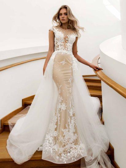 Эффектное свадебное платье-трансформер позволяет подчеркнуть всю красоту фигуры невесты. Бежевая подкладка и силуэт «русалка» задают романтичное настроение, которое дополняет и декор из белого кружева по всей длине. Преобразить юбку помогает воздушный верх из тюльмарина. Сзади спинка притягивает взгляд глубоким V-образным вырезом.