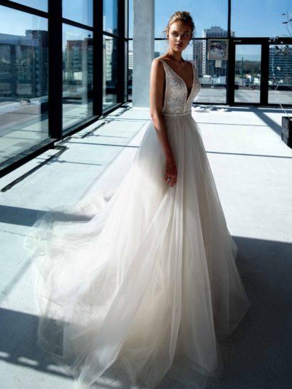 Женственное свадебное платье оттенка слоновой кости. Взгляд притягивает головокружительное V-образное декольте, спускающееся почти до талии.  Оно обрамлено полупрозрачным лифом с отделкой аппликациями.  Спинка свадебного платья также эффектно открыта.  Многослойная юбка со шлейфом идеально дополняет облегающий верх.