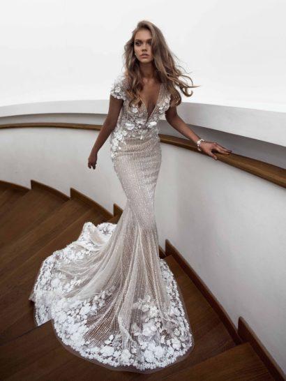 Безупречное свадебное платье облегающего кроя «русалка».  Эффектный полукруг шлейфа делает юбку еще более драматичной и притягательной.  Глубокий V-образный вырез на лифе красиво сочетается с лаконичным коротким рукавом.  Верх декорируют объемные аппликации в виде белых цветочных бутонов.  Романтичная отделка располагается и по низу подола.