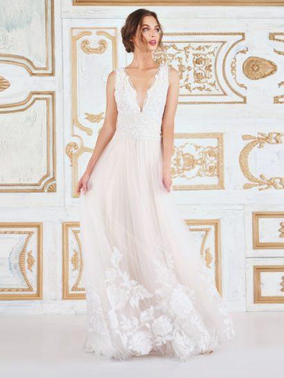 Простое и вместе с тем впечатляющее, это вечернее платье – настоящее совершенство. Вышивка с узором в виде пионов элегантно покрывает верх платья без рукавов и с V-образным вырезом. Нежная юбка из тюля с небольшим шлейфом создает безупречное настроение. Крупные пионы аппликациями завершают великолепный подол.