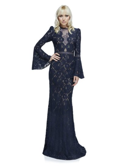 Впечатляющее вечернее платье темно-синего цвета позволяет произвести впечатление на окружающих. По всей длине его покрывает плотное кружево с цветочным мотивом. Дополняют образ невероятные рукава-колокольчики. В области декольте создана иллюзия прозрачности. Для элегантности и комфорта платье дополняет трикотажная подкладка.