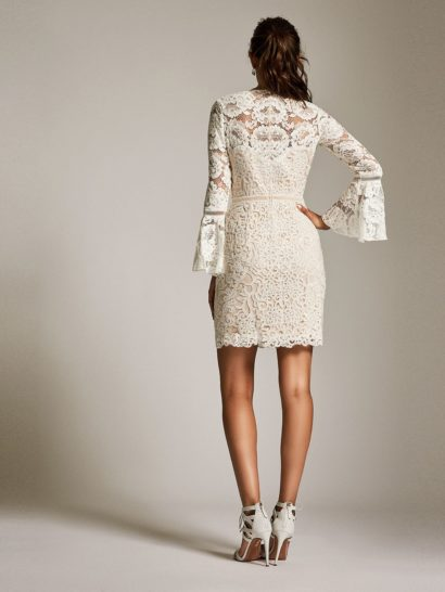 Белое коктейльное платье с длинным рукавом оригинального кроя и закрытым верхом.