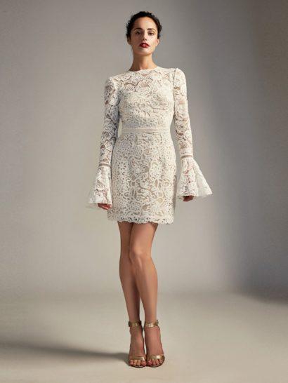 Нежное цветочное кружево создает рукава и лиф белого коктейльного платья, покрытого вдохновленной растительными мотивами вышивкой. Высокий вырез декольте смотрится лаконично и элегантно. Отделка тесьмой выделяет линию талии и украшает рукава, которые спускаются ниже запястья. По всей длине платье оформлено плотной подкладкой.