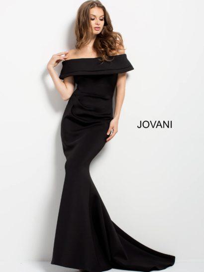 Стильное вечернее платье черного цвета с облегающим кроем и небольшим шлейфом.  Внимание притягивает лиф с открытыми плечами, оформленный объемной оборкой.  Деликатные складки на естественной линии декольте подчеркивают силуэт, спинка изящно дополнена скрытой молнией.