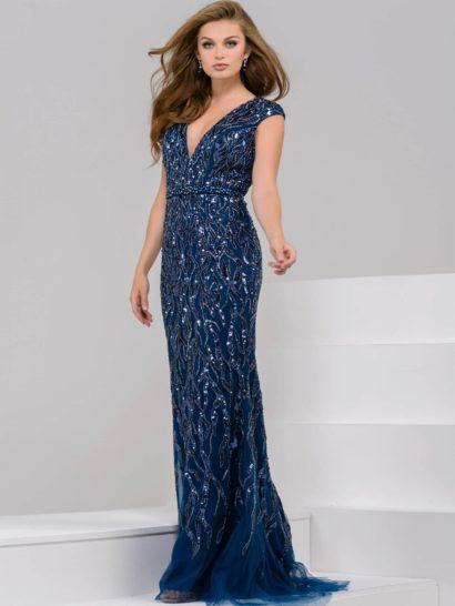 Женственное вечернее платье темно-синего цвета по всей длине дополнено подкладкой. В роли отделки – изящная сияющая вышивка. Деликатный V-образный вырез обрамлен широкими бретелями, а талию выделяет узкий пояс. Закрытая спинка и небольшой шлейф наполняют образ элегантностью.