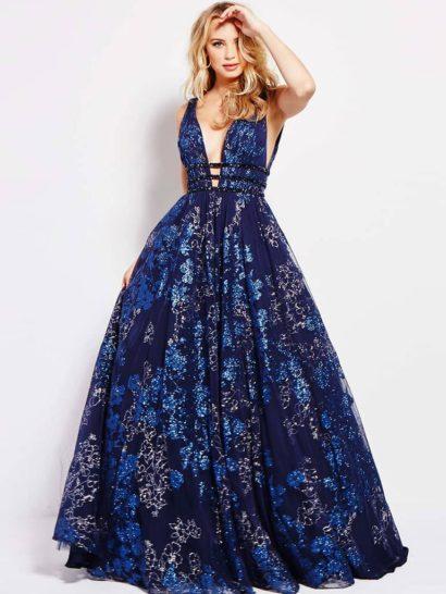 Впечатляющее вечернее платье с юбкой А-силуэта длиной в пол. Роскошная темно-синяя ткань дополнена глянцевым цветочным рисунком. Глубокий V-образный вырез до талии оригинально дополнен двумя узкими поясами. Сзади платье открыто эффектным декольте.