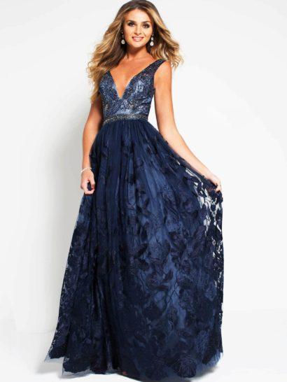 Женственное вечернее платье А-силуэта из темно-синей ткани. Юбка дополнена полупрозрачным верхом с эффектными кружевными аппликациями с цветочным мотивом. Элегантный V-образный вырез дополнен широкими бретелями и сияющим поясом на естественной линии талии.