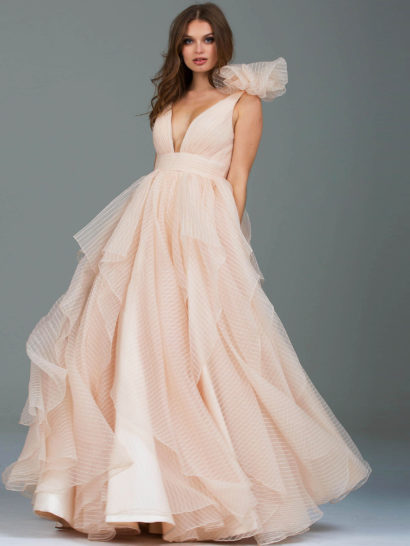 Потрясающее вечернее платье романтичного оттенка шампанского. Пышная юбка выполнена из множества ярусов полупрозрачной ткани с выразительной фактурой. Лиф с глубоким V-образным вырезом дополнен объемным бантом на плече. На спинке также располагается эффектное декольте.