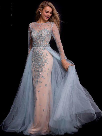 Шикарное вечернее платье прямого кроя с романтичной верхней юбкой из прозрачной ткани.  Теплый пудровый оттенок прекрасно оттеняет голубоватое сияние стразов, роскошным узором спускающихся по закрытому лифу.  Спинка декорирована полупрозрачной вставкой, из такой же тонкой ткани выполнены и длинные прямые рукава.