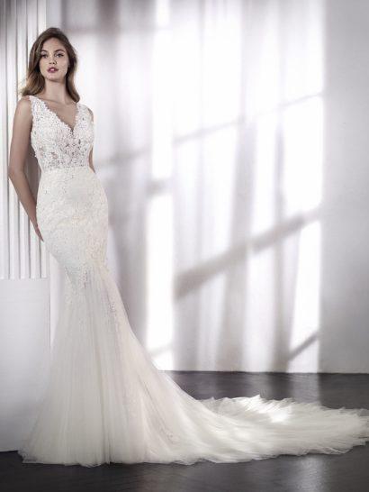 Впечатляющее свадебное платье силуэта «русалка» с эффектом отдельного верха.  Роскошная юбка, облегающая бедра, выполнена из расшитого вышивкой тюля с аппликациями.  Лиф с V-образным вырезом на декольте и спинке дополнен кружевными бретелями.  Платье дополняет съемная подкладка, которую можно использовать под кружевом, чтобы верх был не таким прозрачным.
