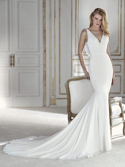 Это одно из тех платьев, в которые влюбляешься с первого взгляда. Невероятно элегантный силуэт «русалка», выполненный из жоржета, отличается струящейся юбкой, полной динамизма. Это облегающее свадебное платье прекрасно подчеркнет женственность изгибов и сделает акцент на декольте V-образным вырезом с драпировками. На спинке – сияющая отделка, украшающая V-образный вырез каскадом камней, наполняющих образ индивидуальностью и стилем.