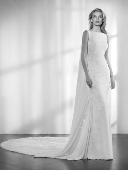 Изысканное и невероятно стильное – вот лучший способ описать это свадебное платье силуэта «русалка» без рукавов, выполненное из крепа с вышивкой и аппликациями.  Струящаяся ткань контрастно сочетается на спинке с сияющей отделкой и вышивкой на тюле, создающей эффект «второй кожи».  Спереди – вырез «лодочка», который смотрится невероятно элегантно.