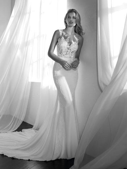 Утонченное и романтичное свадебное платье «русалка», созданное из крепа и тюля. Струящиеся ткани обеспечивают наряду легкость и динамичность. Струящаяся юбка красиво сочетается с верхом, оформленным сияющей вышивкой. Тонкая ткань создает иллюзию обнаженности на декольте и спинке, что смотрится очень чувственно. Шифон, спускающийся с плеч, подчеркивает динамичность, отличающую этот образ.