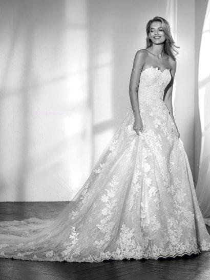 Романтичное сочетание кружева и тюля создает изысканное бальное свадебное платье, очерчивающее талию.  В силуэте сочетаются пышная юбка со шлейфом и облегающий корсет с открытой спинкой и вырезом «сердечком».  Платье по всей длине декорировано изысканной вышивкой и сияющими акцентами, наполняющими образ светом.